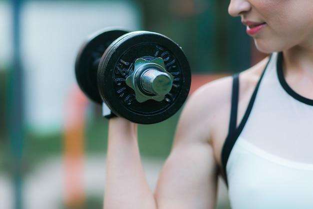 Entrenamiento de mujer con mancuerna al aire libre, bíceps ejercicio primer plano