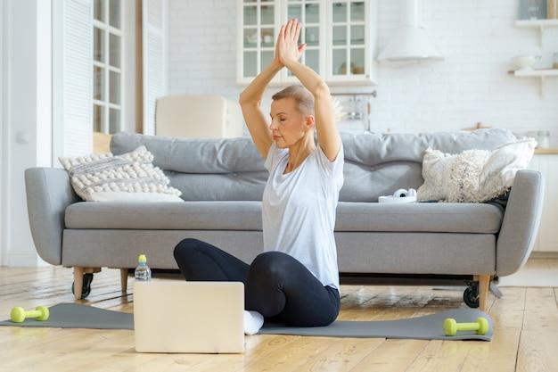Entrenamiento de la mujer mayor en casa con su computadora portátil