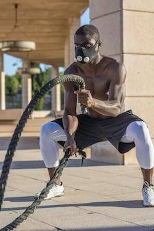 Entrenamiento muscular masculino con cuerdas de combate y máscara de entrenamiento.