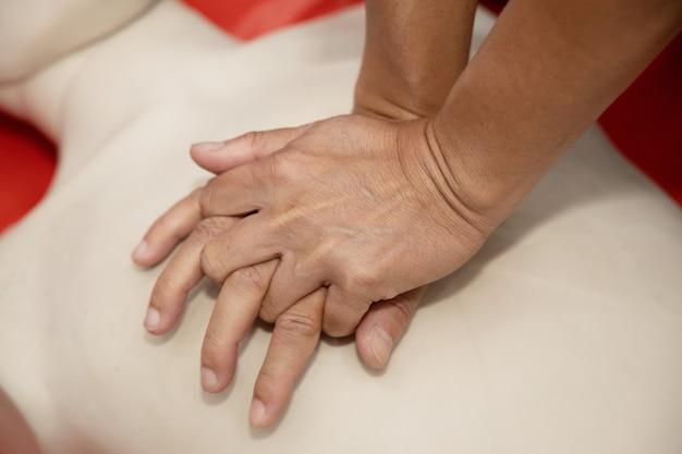 Entrenamiento en primeros auxilios con rcp con la mano sobre el maniquí de cuerpo entero