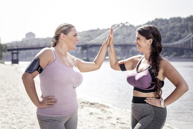 Entrenamiento productivo. mujeres positivas alegres dando cinco el uno al otro mientras están de pie en la playa después del entrenamiento
