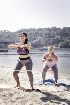Entrenamiento productivo. mujeres positivas felices haciendo abdominales mientras usan banda elástica para entrenar