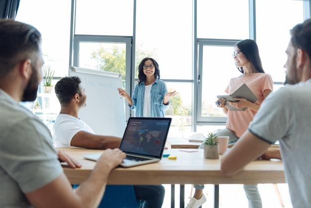 Entrenamiento profesional. personas curiosas e inteligentes encantadas que miran a su formadora y la escuchan mientras asisten a un curso.