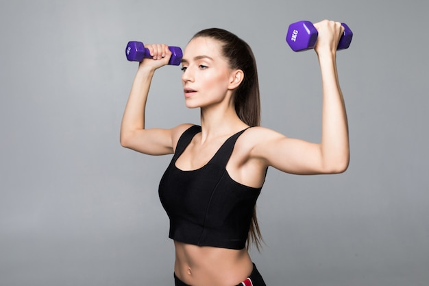 Entrenamiento sonriente de la mujer de la aptitud con pequeñas pesas de gimnasia aislado en la pared blanca