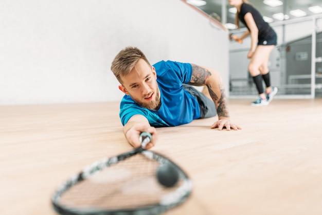 Entrenamiento de squash, jugador masculino con raqueta se encuentra en el suelo.
