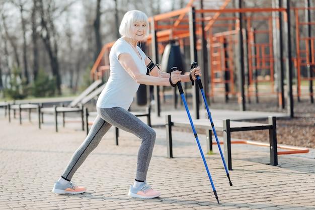 Entreno duro. alegre mujer rubia sonriendo y usando muletas mientras hace ejercicio