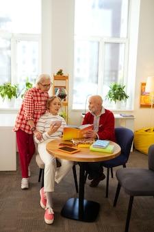 Entretenimiento agradable. agradables personas mayores hablando de libros mientras disfrutan de su tiempo juntos