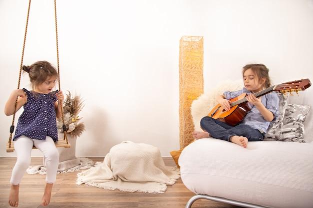 Entretenimiento en casa, dos hermanitas juegan juntas. desarrollo de los niños y valores familiares. el concepto de amistad y familia de los niños.