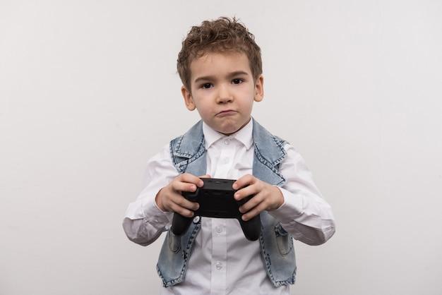 Entretenimiento moderno. lindo chico agradable de pie contra el fondo blanco mientras juega un videojuego