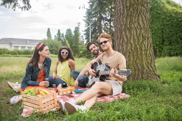 Entretenimiento, picnic. cuatro jóvenes amigos alegres con comida y bebidas de guitarra con un día de picnic juntos en el parque verde
