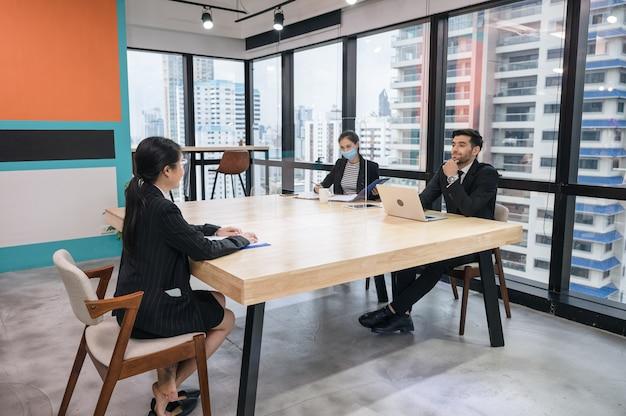 Entrevista de trabajo del empleador de recursos humanos del cáucaso con la secretaria y la joven solicitante asiática en la oficina moderna