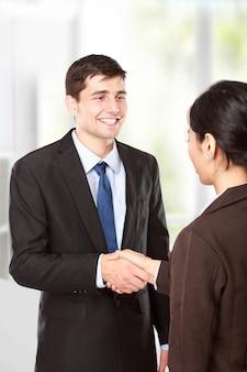Entrevistador dándole la mano al futuro empleado