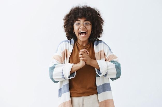 Entusiasta, activa y despreocupada, chica optimista de piel oscura con gafas y un atuendo elegante, juntando las manos cerca del pecho y sonriendo ampliamente, emocionada con una gran noticia contándola al resto de la gente.