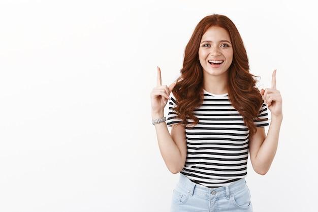 Entusiasta ambiciosa joven alegre con cabello pelirrojo y pecas, riendo felizmente introducir promo, levantando las manos apuntando hacia arriba, sonriendo con dientes, recomendar la mejor oferta, pared blanca