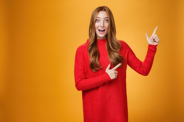 Entusiasta y ambiciosa mujer pelirroja linda con pecas en vestido rojo apuntando a la esquina superior derecha sonriendo asombrada y curiosa mientras explora un nuevo espacio impresionante posando sobre fondo naranja