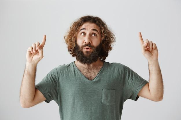 Entusiasta chico barbudo del medio oriente apuntando con el dedo hacia arriba y mirando intrigado