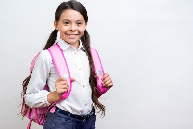 Entusiasta colegiala hispana de pie con mochila.