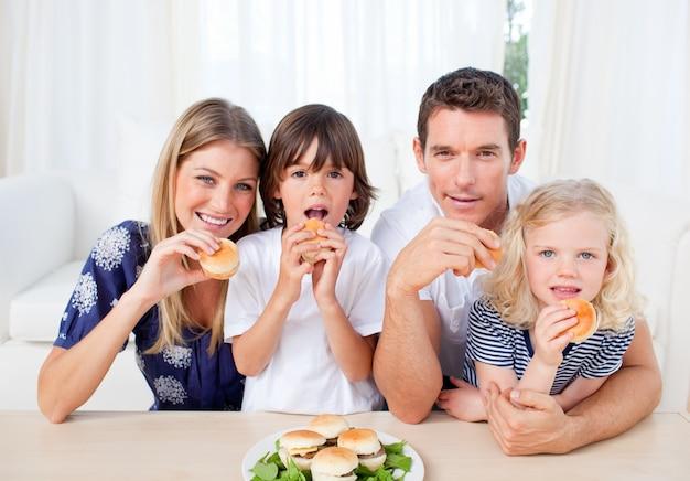 Entusiasta familia comiendo hamburguesas en la sala de estar