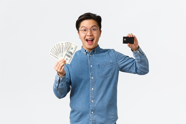 Entusiasta hombre de negocios asiático joven que muestra dinero y tarjeta de crédito recibe los primeros ingresos del personal.