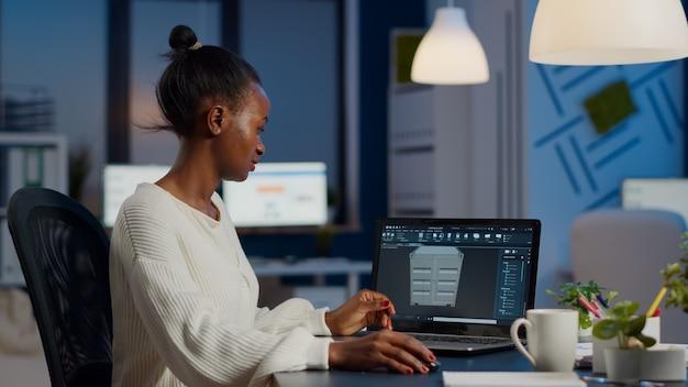 Entusiasta ingeniero africano analizando software cad para diseñar un concepto 3d de contenedor trabajando horas extras en una empresa de nueva creación para el prototipo