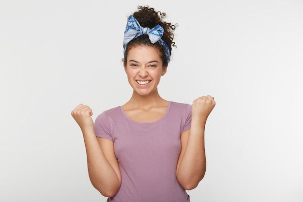 Entusiasta motivada atractiva joven dando puños en gesto de victoria y éxito