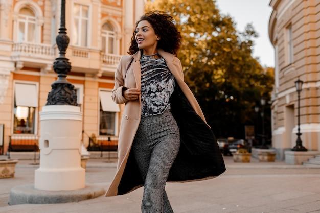 Entusiasta mujer africana en elegante traje casual corriendo y divirtiéndose.