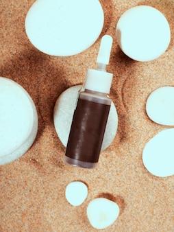 Envasado con piedra de botella de arena. viajes, concepto de vacaciones. crema de protección solar. concepto de verano. fondo de loción cosmética. fondo de verano de playa.