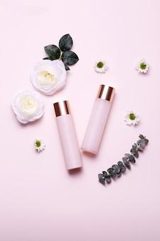 Envase de botella cosmética con hojas verdes aisladas sobre fondo rosa