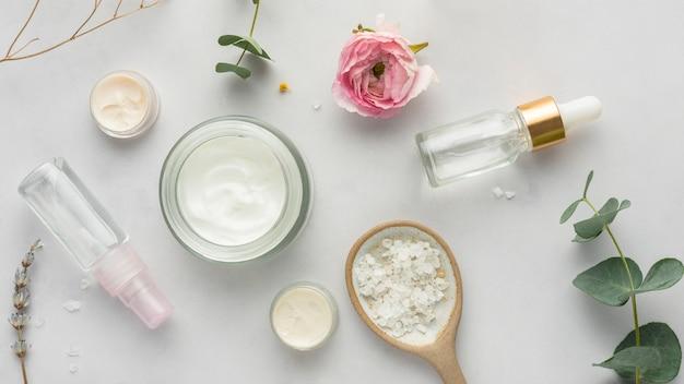 Envase de crema de vista superior, suero y plantas.