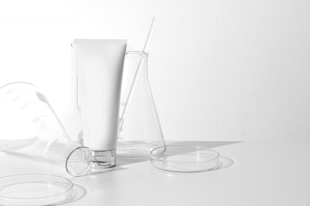 Envase poner crema facial de la belleza cosmética de la loción con la botella de cristal del tubo de ensayo de la ciencia del laboratorio en el fondo blanco
