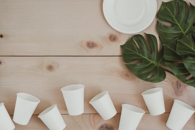 Envases de alimentos de papel, tazas y platos ecológicos desechables, compostables, reciclables y placa con ramas de plantas sobre fondo de madera copia espacio vista superior. concepto de cero residuos