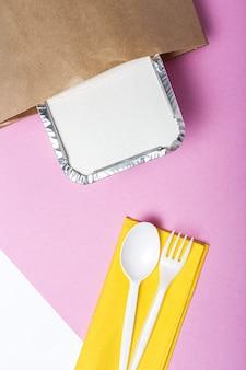 Envases de aluminio para comida para llevar preparados para su entrega en bolsas de papel reciclable. endecha plana