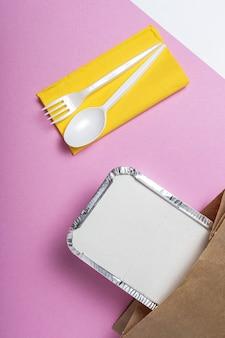 Envases de aluminio para comida para llevar preparados para su entrega en bolsas de papel reciclable.
