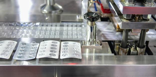 Envases blíster de papel de aluminio plateado para proteger de la luz en la línea de producción concepto farmacéutico industrial