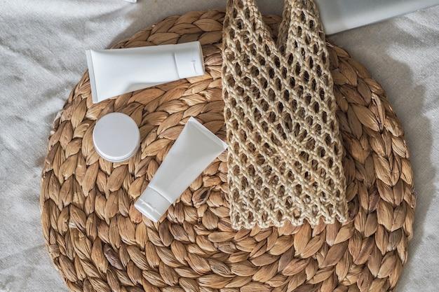 Envases de botellas cosméticas producto blanco con flores secas y bolsos tejidos.