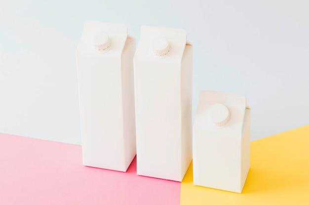 Envases de cartón de leche sobre tabla brillante.