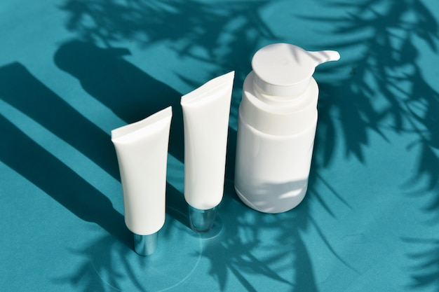Envases de envases de botellas cosméticas con hojas de sombra y efecto de luz, etiqueta en blanco para marca orgánica, concepto de producto de belleza para el cuidado de la piel natural.