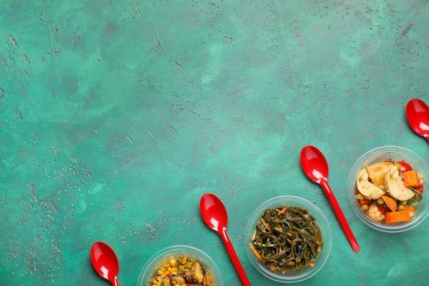 Envases de plástico con comida deliciosa sobre fondo de color