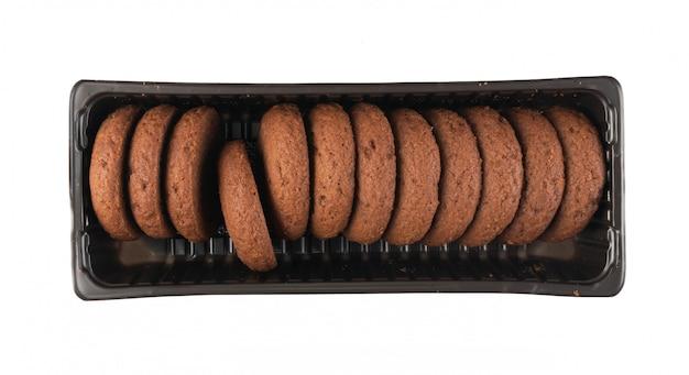 Envases de plástico con galletas de mantequilla de chocolate suave con relleno de chocolate aislado en la vista superior de fondo blanco.