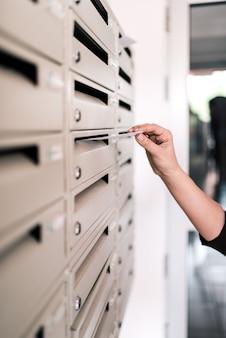 Enviando mensaje. poner carta en buzón en el pasillo, primer plano.