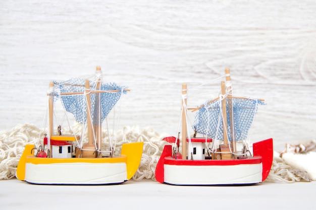 Envíe juguetes y conchas marinas y ne en la pared de madera blanca de cerca