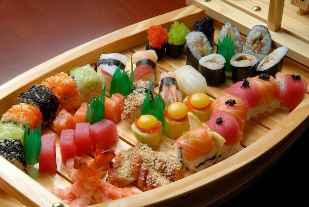 Envíe con sushi y rollos sobre una superficie oscura