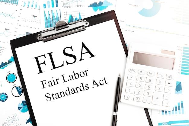 Envíe el texto flsa - fair labor standards act en el portapapeles, bolígrafo, calculadora, gráficos. concepto de negocio. endecha plana.