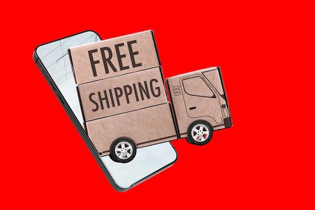 Envío gratuito escrito en un remolque de madera que sale de un teléfono inteligente sobre fondo rojo.
