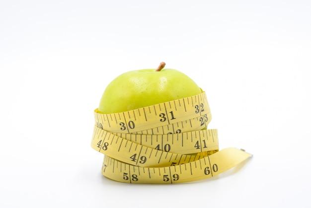 Envoltura de manzana verde mediante cinta métrica para medir la longitud en un estilo de vida saludable, blanco y dietético