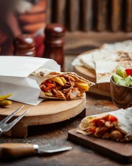 Envoltura de pan plano de pollo con papas fritas, tomate y espinas en una bolsa de papel para llevar