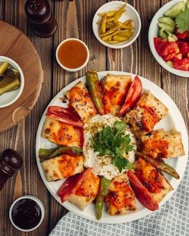 Envolturas de beyti kebab servidas con yogurt, pimiento asado y ensalada