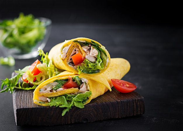 Envolturas de tortilla fresca con pollo y verduras frescas sobre tabla de madera. burrito de pollo. cocina mexicana. copia espacio