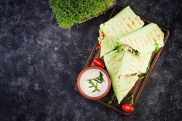 Envolturas de tortilla fresca con pollo y verduras frescas sobre tabla de madera. burrito de pollo. concepto de comida sana. cocina mexicana. vista superior, arriba