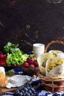 Envolturas de tortilla con pollo asado y vegetales, jugos, vegetales y bayas, baguette y queso.